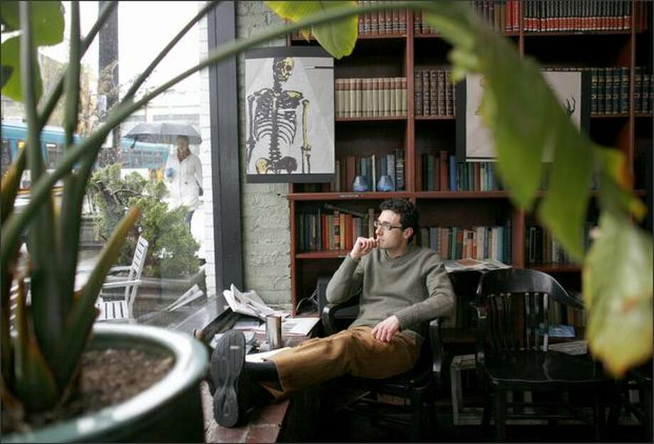 Jerry Romano relaxes at Bauhaus Books and Coffee on East Pine Street in Seattle. Romano has lived in the neighborhood since 1994 and has seen it change dramatically. Bauhaus is an example of the character that some are trying to maintain in the neighborhood. Photo: Joshua Trujillo/seattlepi.com