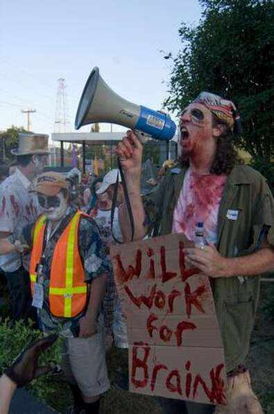 A zombie organizer shouts directives into his megaphone before the start of a Thriller dance featuri