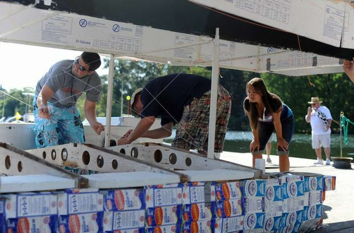 The Museum of Flight team works on its space shuttle boat before the races at Seattle's Seafair Milk Carton Derby on Green Lake Saturday.