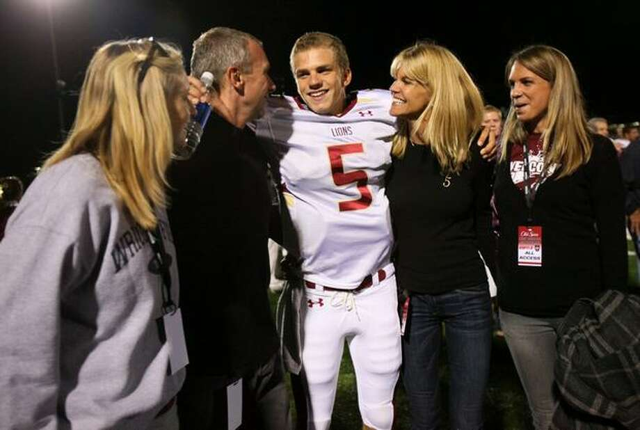 Oaks Christian player Nick Montana is embraced by his family, including father and legendary quarterback Joe Montana and mother Jennifer after defeating Skyline High School on Friday September 18, 2009. Photo: Joshua Trujillo, Seattlepi.com