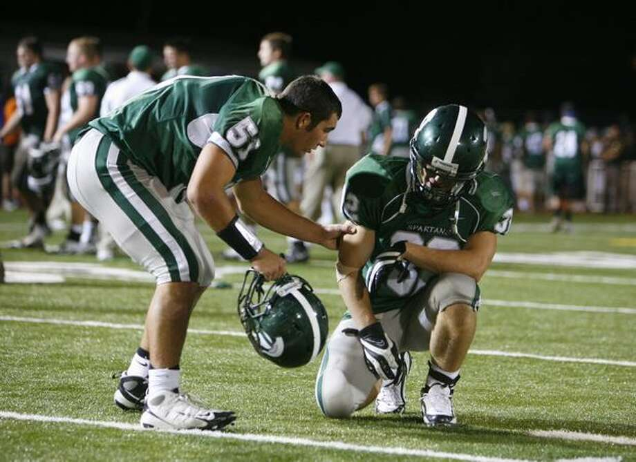 Skyline High School player Anthony De Matteo (51) comforts teammate Nick Washburn (32) after Skyline was defeated by nationally-ranked Oaks Christian High School on Friday September 18, 2009. Photo: Joshua Trujillo, Seattlepi.com