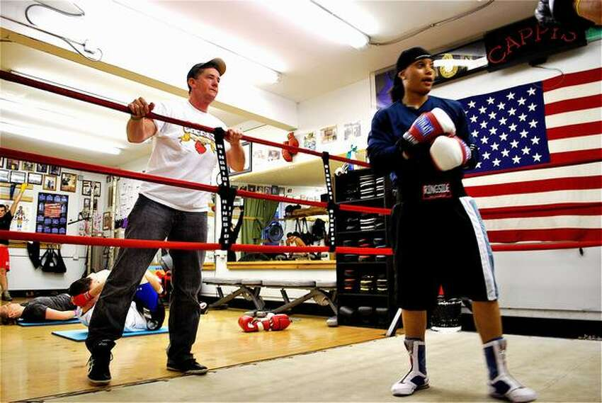 Cap Kotz, Queen Underwood's coach, provides pointers to Underwood during a boxing lesson. Kotz has owned Cappy's Boxing Gym since the mid-1990s. Kotz grew up in Washington and Montana watching his dad box in the Army. He was a boxer, too, before going on to coach.