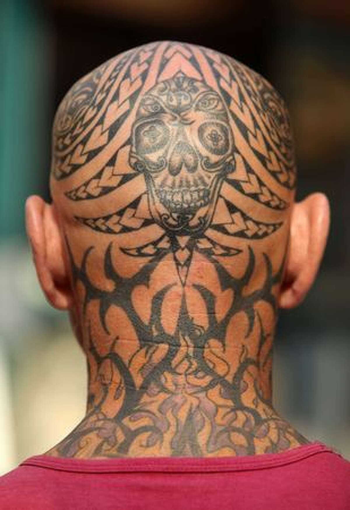 A man shows off his tattooed head on the opening day of the fifth London Tattoo Convention in London, England.