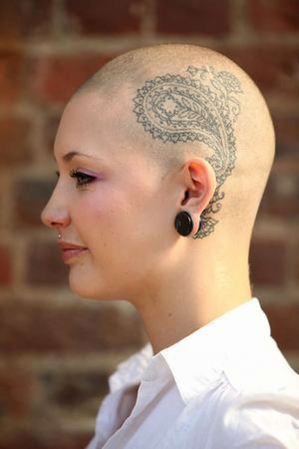 Tattoo enthusiast Camilla Caney shows off her tattooed head on the opening day of the fifth London Tattoo Convention in London, England.