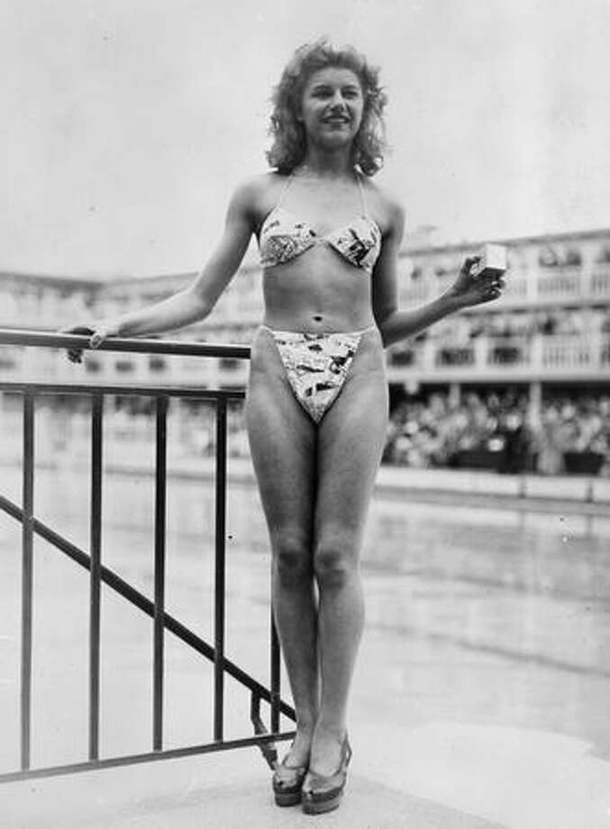 "July 5, 1946: Shortly after the test of a nuclear explosion in a South Pacific atoll named Bikini, French fashion designer Louis Reard introduced a swimsuit of the same name, hoping that the new outfit would cause a similarly explosive reaction. It's fair to say that he succeeded. ""The new 'Bikini' swimming costume (in a newsprint-patterned fabric) ... caused a sensation at a beauty contest at the Molitor swimming pool in Paris,"" the caption reads. ""... Reard was unable to find a 'respectable' model for his costume and the job of displaying it went to 19-year-old Micheline Bernardini, a nude dancer from the Casino de Paris. She is holding a small box into which the entire costume can be packed."" Photo: Getty Images"