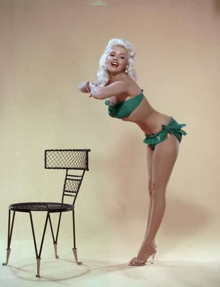 Circa 1955: American actress and sex symbol Jayne Mansfield leans forward from the waist and clasps her hands together in a studio portrait. She wears a green bikini and clear high-heel shoes. Photo: Getty Images