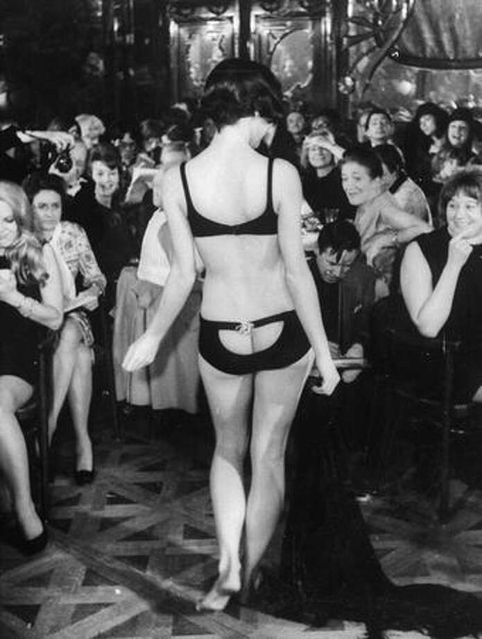 January 1968: A designer swimsuit with a peekaboo rear designed by actress Elizabeth Taylor and her American partners Mia Fonssagrieves and Vicki Tiel on show at Maxim's in Paris. Photo: Getty Images