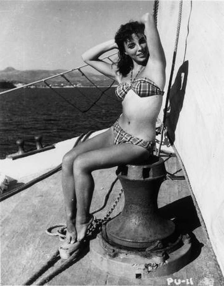 "1955: British actress Joan Collins enjoys a sail in the sunshine of the Pacific. She was in Hollywood to play Bess Throckmorton, one of Elizabeth I's maids of honor in ""The Virgin Queen."" Photo: Getty Images"