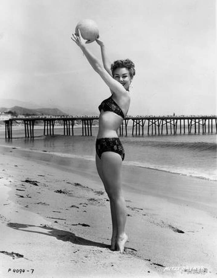 "1955: American actress Mitzi Gaynor, wearing a bikini, holds a volleyball over her head in a full-length promotional portrait for director Robert Lewis' film, ""Anything Goes."" Photo: Getty Images"