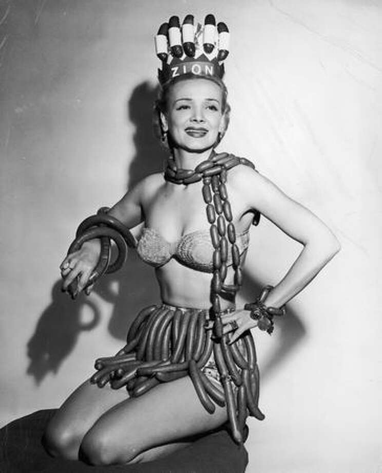Circa 1955: For the Donut Queen, it could have been worse. Actress Geene Courtney models a scarf, skirt, bracelets and a crown made from hot dogs, frankfurters, and kielbasa in her role as Queen of National Hot Dog Week, as selected by the Zion Meat Products Company. Photo: Getty Images