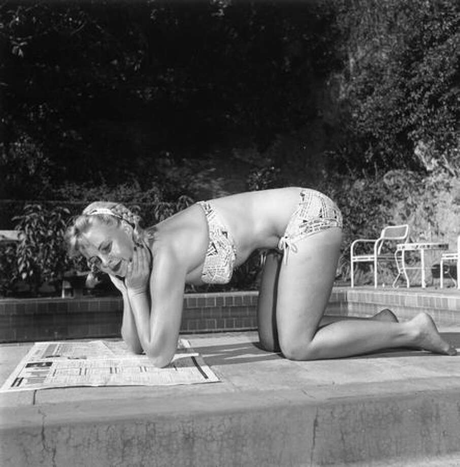 """October 1951: One of our's favorites — """"Miss Newsprint"""" — wears a newspaper-patterned bikini. Photo: Getty Images"""