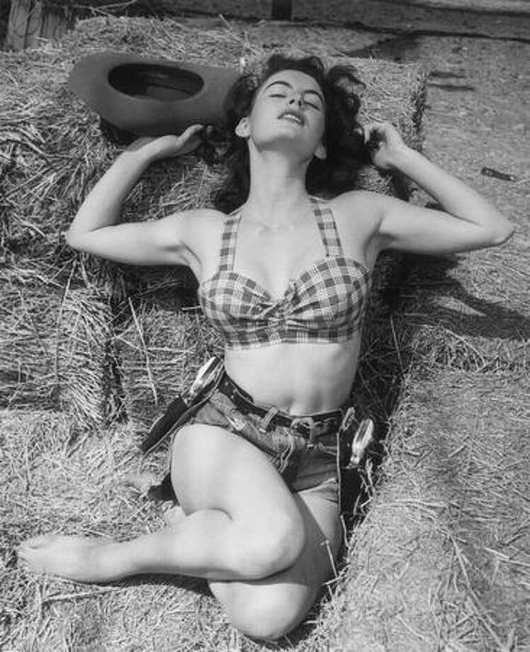 Circa 1955: A studio portrait of B-movie actor and model Mona Knox, wearing a holster belt with guns, denim shorts, and a bikini top. This apparently gives her a warm and sensuous feeling, though we're not exactly sure why. Photo: Getty Images