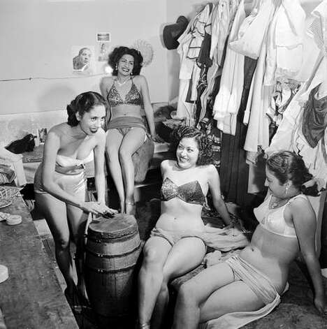 1952: Bikini-clad chorus girls in a burlesque show relax backstage by beating out a rhythm on a native drum, at the Tivoli Theatre in Mexico City. Photo: Getty Images