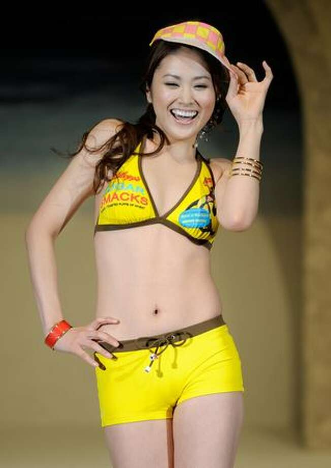 As bikinis have gained in popularity outside the Western world, there are some surprises. Asian designers and models seem to have a good deal more fun with the bikini; this Japanese model advertises as U.S. cereal on her way to the beach. Photo: Getty Images