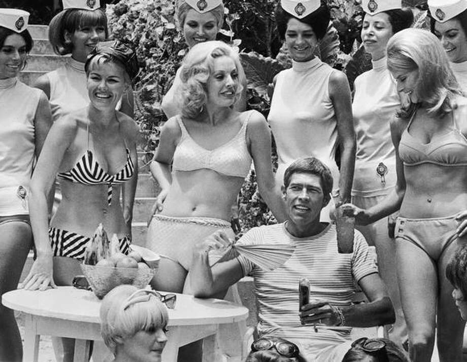 "1967: Actor James Coburn carries on the Bond tradition, surrounded by young women in bikinis and white uniforms in a still from the film ""In Like Flint."" Photo: Getty Images"