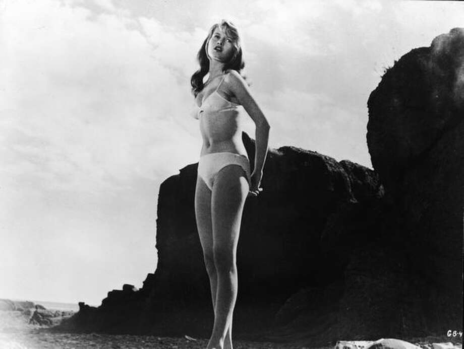 "1958: Soon they were making movies based on the subject. French-born actress Brigitte Bardot wore a white bikini and stood on a rocky beach in a still from the film, ""The Girl in the Bikini."" Photo: Getty Images"