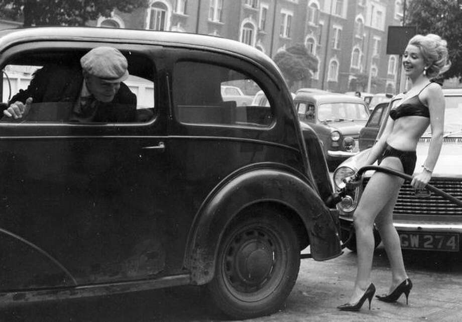 August 1965: This won't be the last example of bikini-clad women being used to sell automotive services. A driver at the head of a queue of cars casts a look back at bikini-clad Mari Rennie, as she serves his car a free gallon of gas as a gimmick to attract customers during a price war amongst gas companies in England. Photo: Getty Images