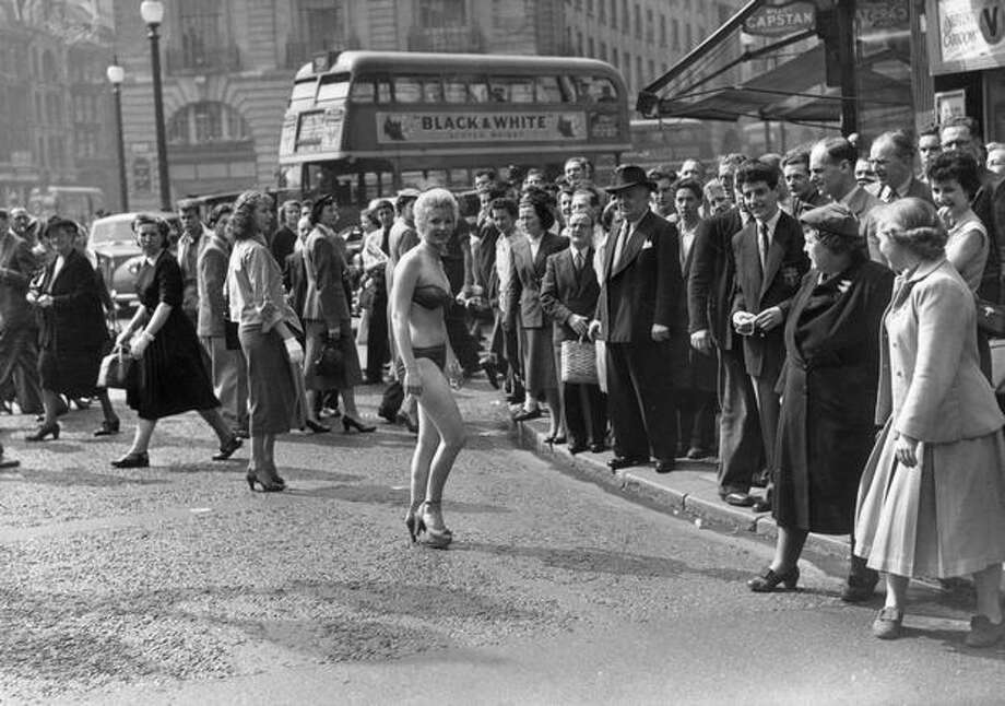 April 1952: 19-year-old usherette Margaret Lewis from Carmaethen, Wales, causes a stir in London's Piccadilly when she decides to beat the heat wave and travel to work clad only in bikini and high heels. Photo: Getty Images