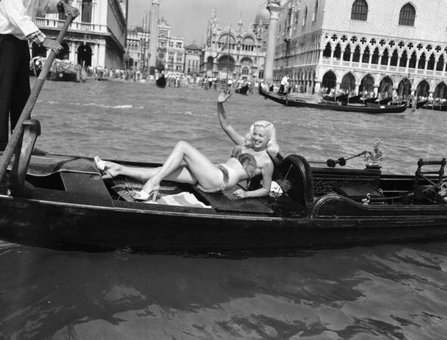 May 1955: The poor man's Jayne Mansfield, British actress Diana Dors, wears a mink bikini while riding in a gondola by St. Mark's Square, Venice, during the Venice Film Festival. Photo: Getty Images