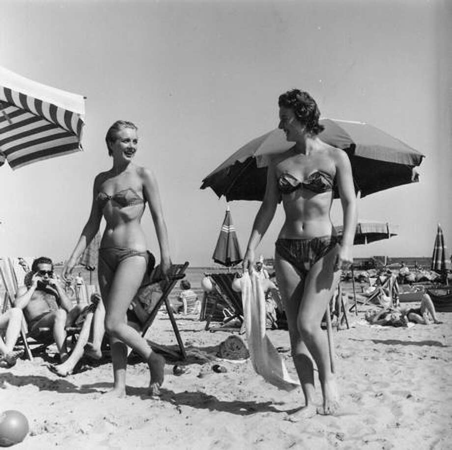 July 1955: Models wear the latest bikini fashion at a beach on the French Riviera, where some time later it would become fashionable to wear only half the suit. Photo: Getty Images