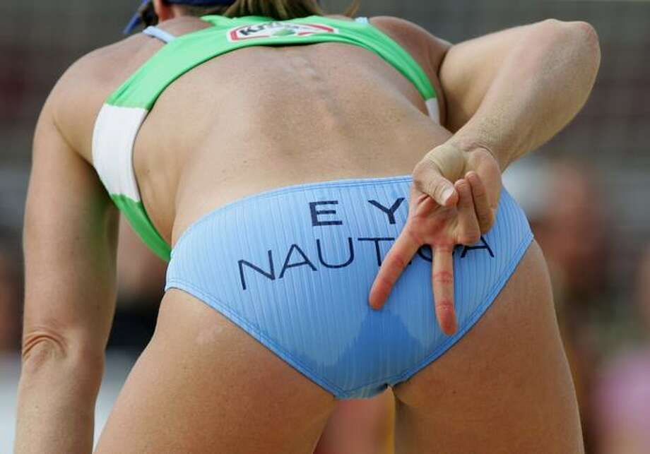 Bikinis worm their way into the sports world: Elaine Youngs of the U.S. signals the next play behind her bikini bottom during a match in the Beach Volleyball World Championships in Berlin, Germany. The inclusion of this sport in the Olympics has boosted its popularity enormously; could it have something to do with, oh, say, THE BIKINIS? Photo: Getty Images