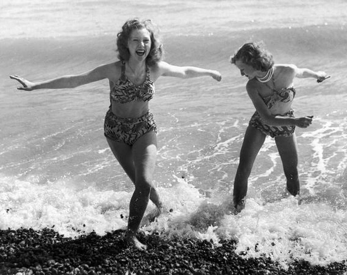 The world had seen two-piece bathing suits for women before, but perhaps none so liberating, or as apt for the times, as the bikini. As a post-war sense of relief, security and greater prosperity settled over the Western world, women embraced its liberating design. Here, Shirley Waller (left) and Jean Gullet enjoy a day at the beach in Hastings, East Sussex, on the south coast of England in April 1950.