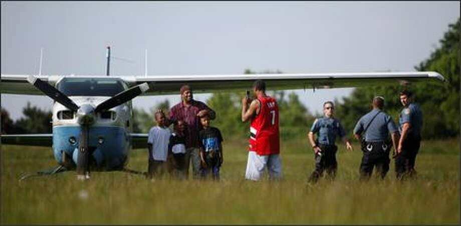 Russell Hebert Jr., center in red, takes a photo of his family with the plane in the background. The Cessna made an emergency landing Monday at Genesee Park. | Photo gallery Photo: Clifford DesPeaux/seattlepi.com