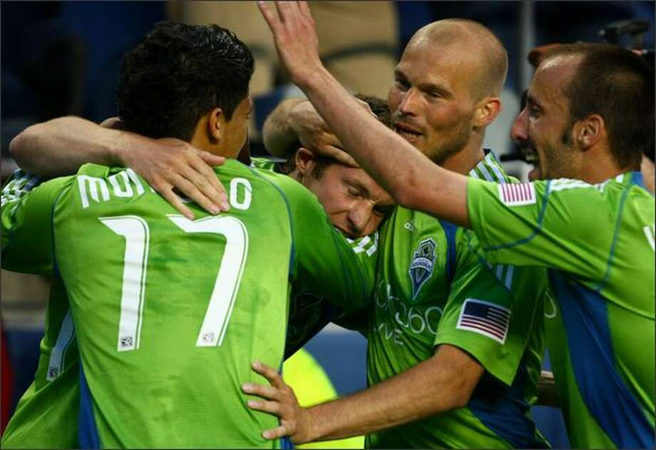 Seattle Sounders players, from left, Fredy Montero (17), Nate Jaqua, Freddie Ljungberg and Peter Vagenas celebrate Jaqua's goal in the second half. Photo: Joshua Trujillo/seattlepi.com