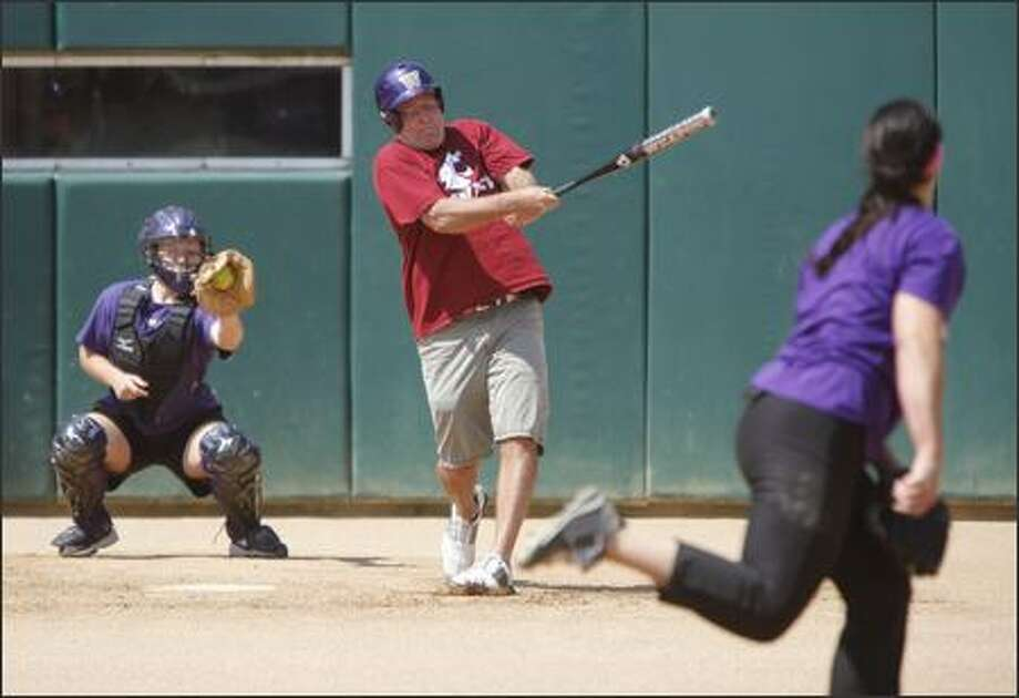 Coug and seattlepi.com columnist Jim Moore swings at a pitch thrown by UW softball star Danielle Lawrie at Husky Softball Stadium on Monday afternoon. Photo: Clifford DesPeaux/seattlepi.com