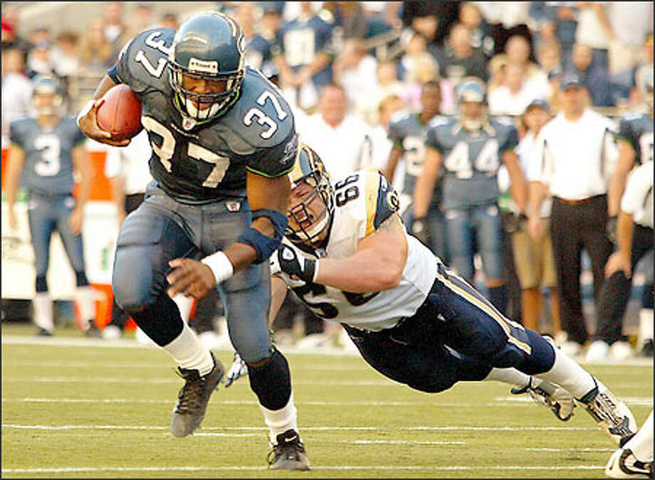 "Shaun Alexander eludes the Rams' Brian Young to gain five yards. Alexander's wife, Valerie, delivered the couple's first child, Heaven, early yesterday afternoon. ""I got to pull the baby out and I got to cut the cord. That was my first catch of the day,"" Alexander said. Photo: Mike Urban, Seattle Post-Intelligencer"