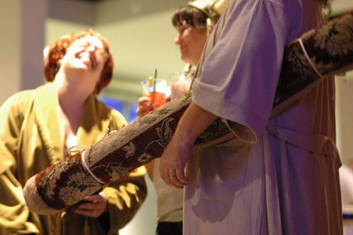 """A """"Big Lebowski"""" fan carries a rolled-up rug during Lebowski Fest at Acme Bowl in Tukwila Tuesday."""