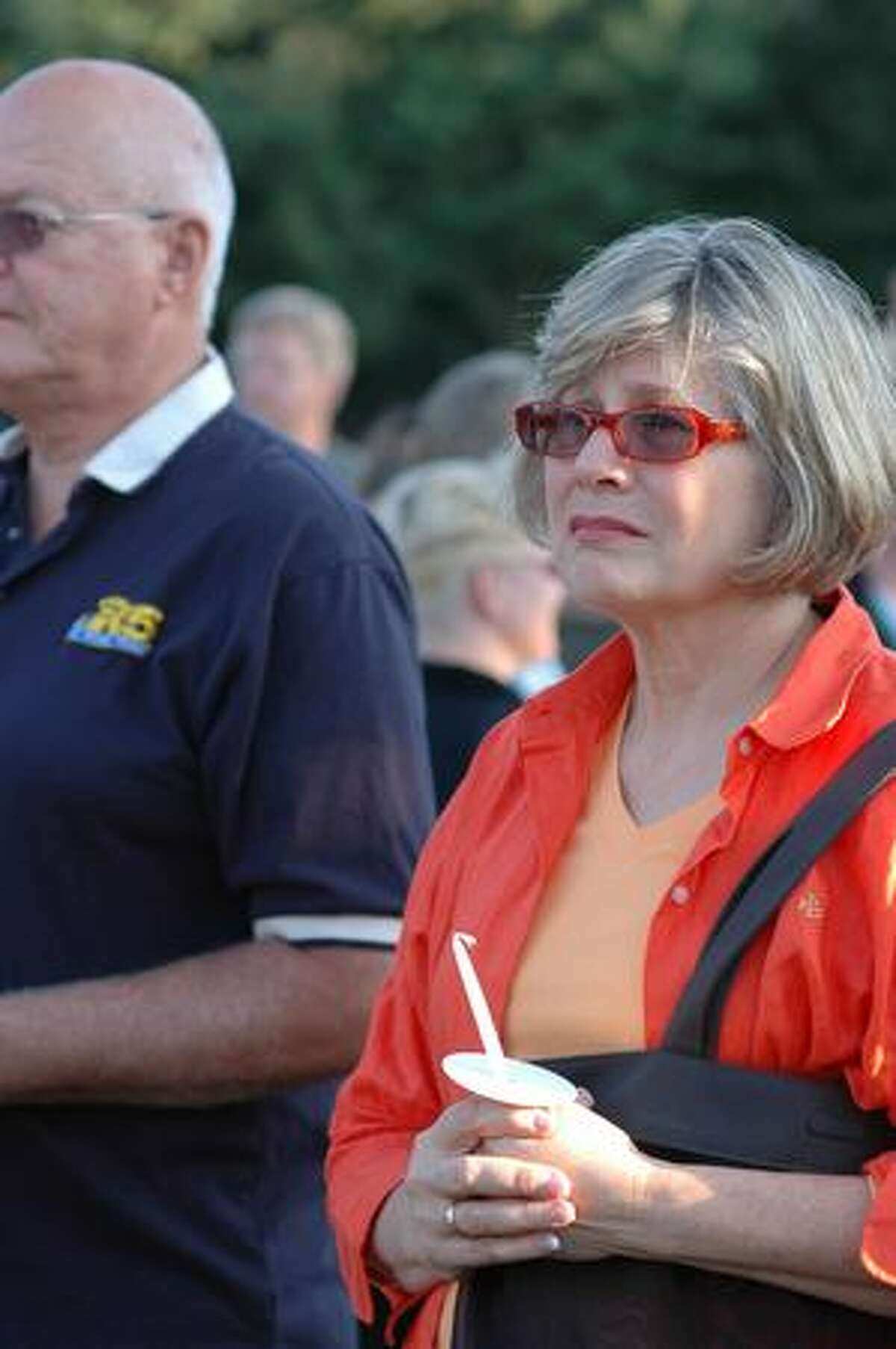 Elizabeth Graham, right, and Bob Cronn watch the start of a candle light vigil for the victim of a stabbing early last week at the South Park Community Center in south Seattle Thursday July 23, 2009. Said Graham,
