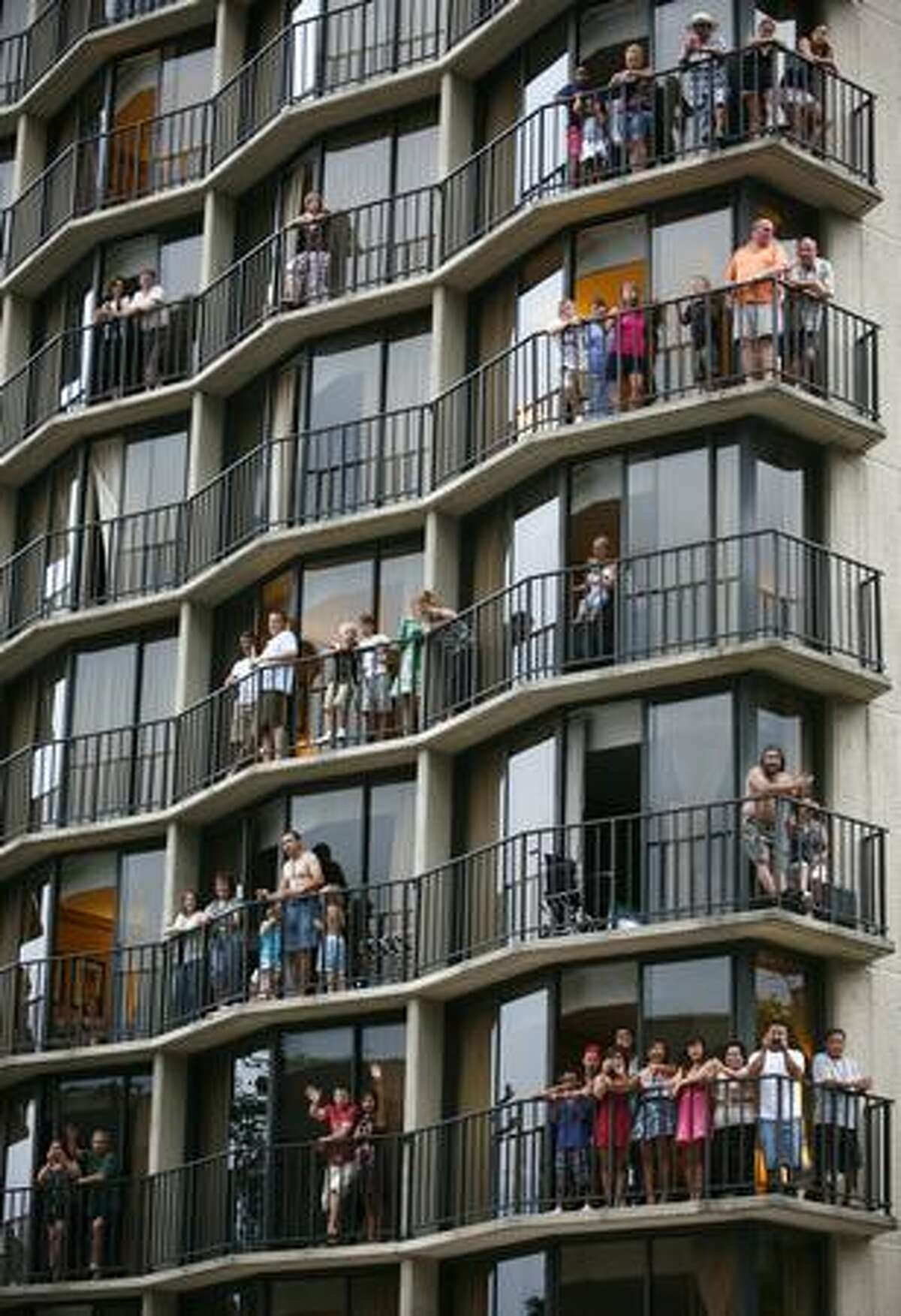 People watch the parade from the Warwick Hotel during the Seafair Torchlight parade on Saturday July 25, 2009 along 4th Avenue in Seattle.