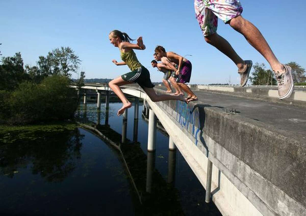 Wendy Collins, center, leaps off an unused ramp on Highway 520 into the cool water of the Arboretum below on Tuesday.