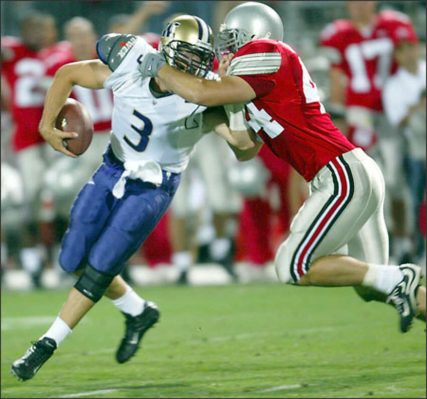 Washington quarterback Cody Pickett is sacked by Ohio State's Robert Reynolds (44) in the second half.
