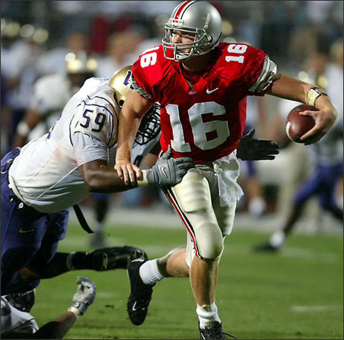 Washington's Jerome Stevens grabs for Ohio State quarterback Craig Krenzel in the second half. Stevens slowed Krenzel enough for Tui Alailefaleula to finish off the sack.