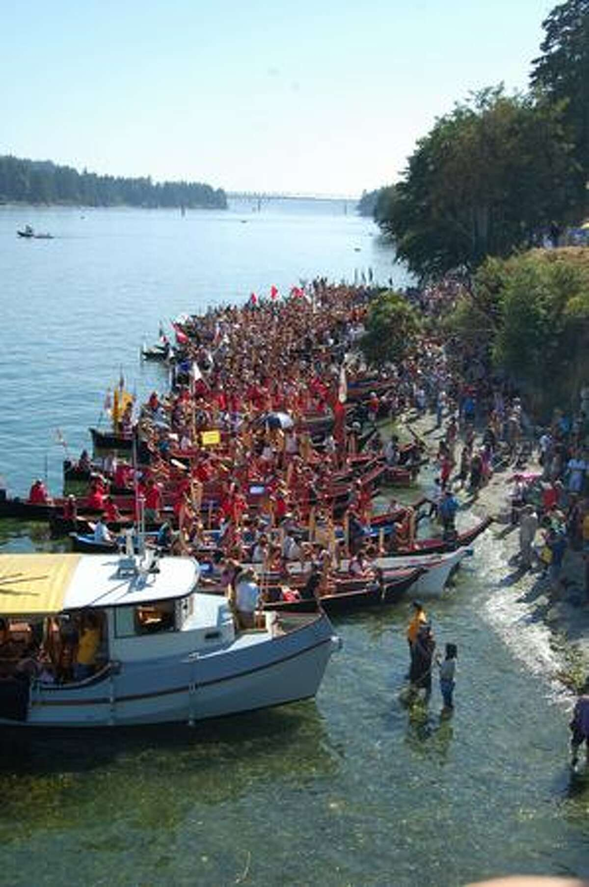 About 100 canoes arrive at the Suquamish shore Monday afternoon as more are en route. Native American canoes from several Northwest tribes took part in the landing, the culmination of an annual event known as