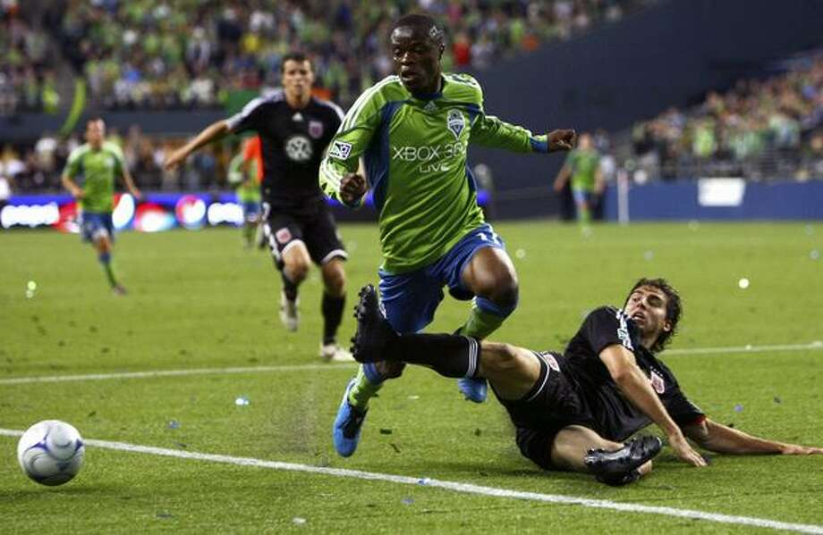 Seattle Sounders' Steve Zakuani, center, and D.C. United's Dejan Jakovic chase the ball in the final minutes. The match ended in a 3-3 draw. Photo: Joshua Trujillo/seattlepi.com