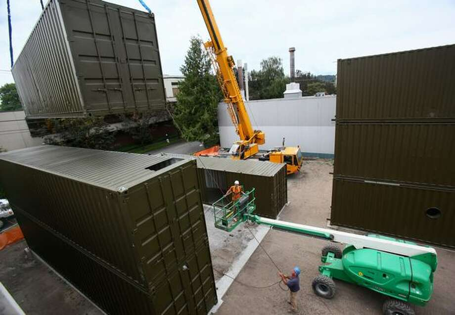 Workers from Fogarty Construction stack shipping containers as they construct a building out of the containers on Thursday in Seattle's Georgetown neighborhood. Photo: Joshua Trujillo/seattlepi.com