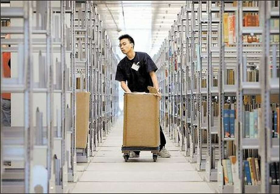 Warren Chin with Hallett Movers pushes a cart filled with books at the Central Library in 2004. Hallett Movers oversaw the transfer of 14 tons -- 2,000,000 books -- from three temporary locations. Photo: / Seattle Post-Intelligencer
