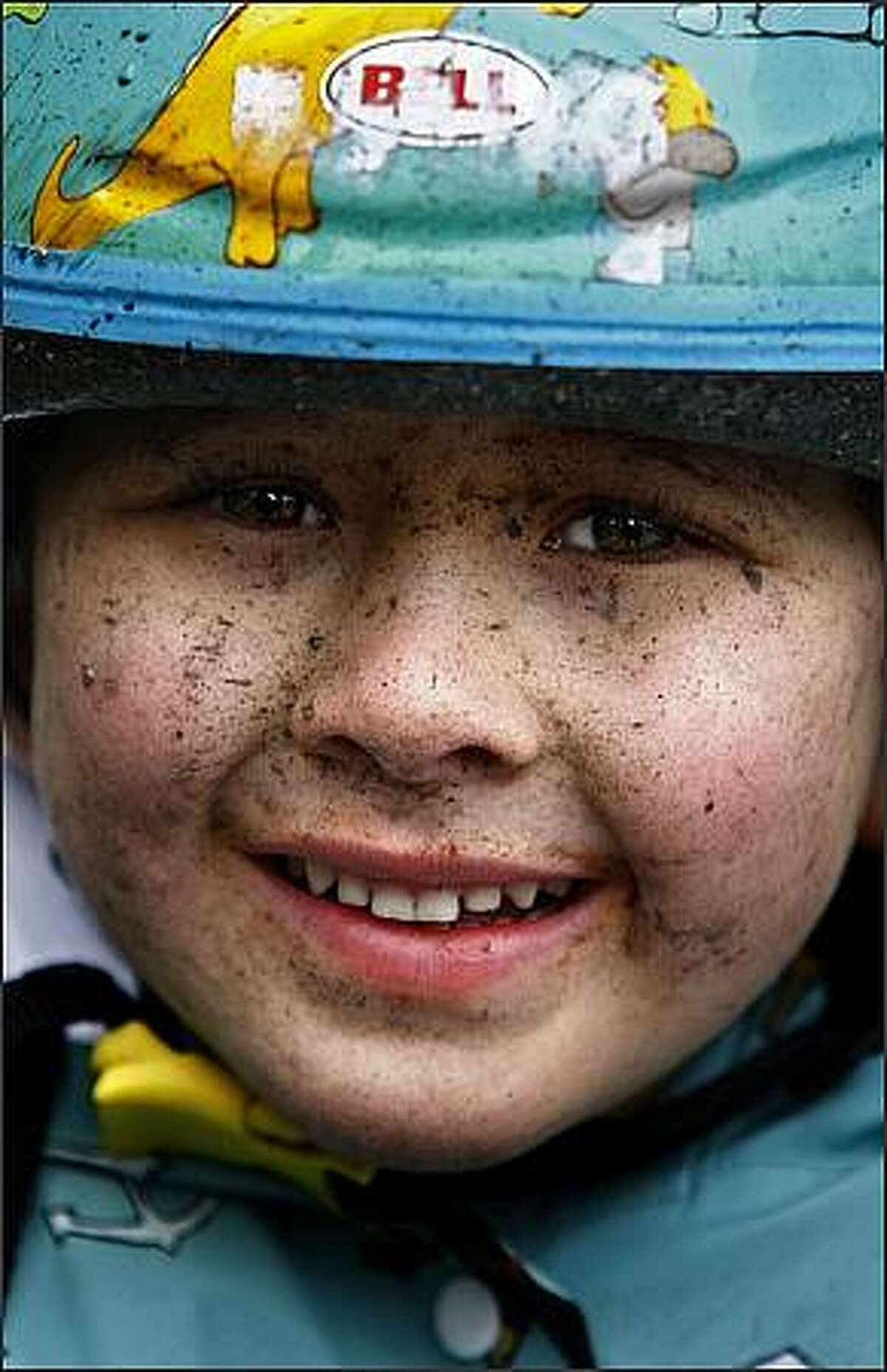 Jonathan Sugimoto, 4, of Poulsbo is smiling despite a dirty afternoon traveling behind his dad during the Chilly Hilly bicycle ride around Bainbridge Island.