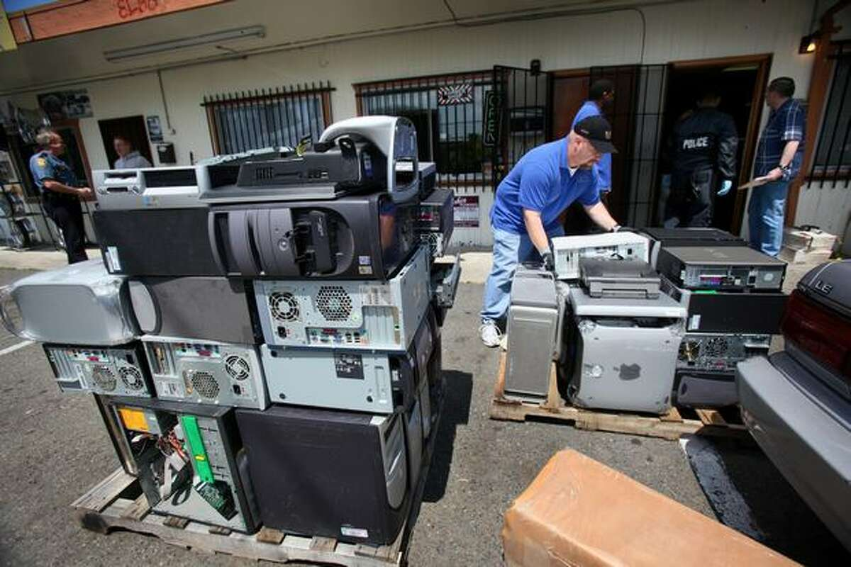 David Matthew, of the Seattle Police Department's evidence collection unit, helps stack computers in front of a business on Rainier Avenue South after police broke up what they say is part of a major computer trafficking ring.