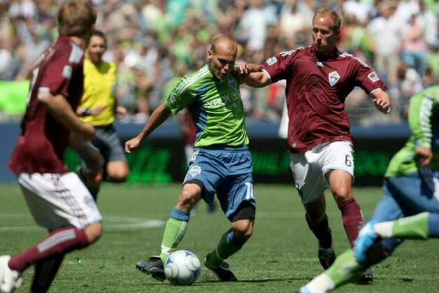 Freddie Ljungberg, center, runs the ball toward the goal as Greg Dalby defends. Photo: Clifford DesPeaux/seattlepi.com