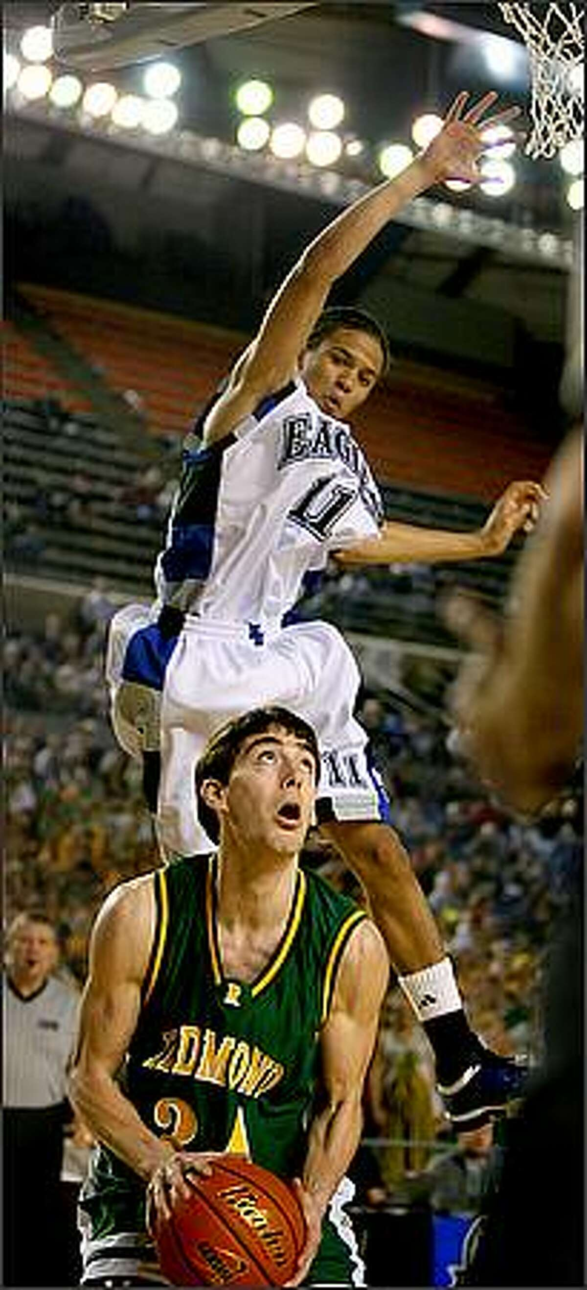Federal Way's Michael Hale gets some elevation as he is faked by Redmond's Chad Hui-Peterson in the first quarter as Federal Way High School battles Redmond High School in the first round of the WIAA Boys' State Basketball Championships at the Tacoma Dome in Tacoma, Wash.