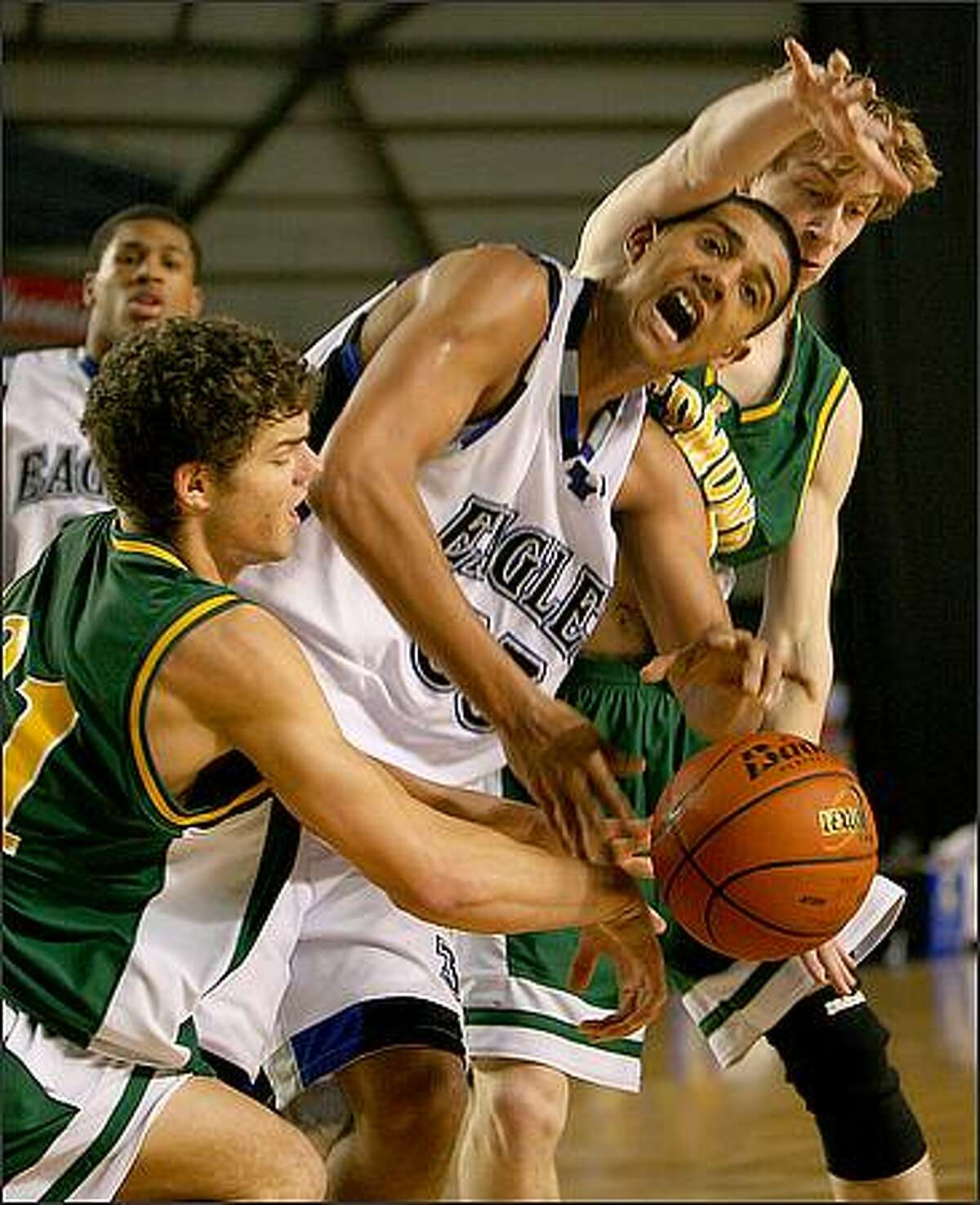 Redmond defenders Max Wisman (left) and Willie Gonia (right) did what they could to try and slow down Federal Way's JT Koontz and the rest of his Federal Way teammates, but couldn't do much as Federal Way High School beat Redmond High School 66-36 in the first round of the WIAA Boys' State Basketball Championships at the Tacoma Dome in Tacoma, Wash.