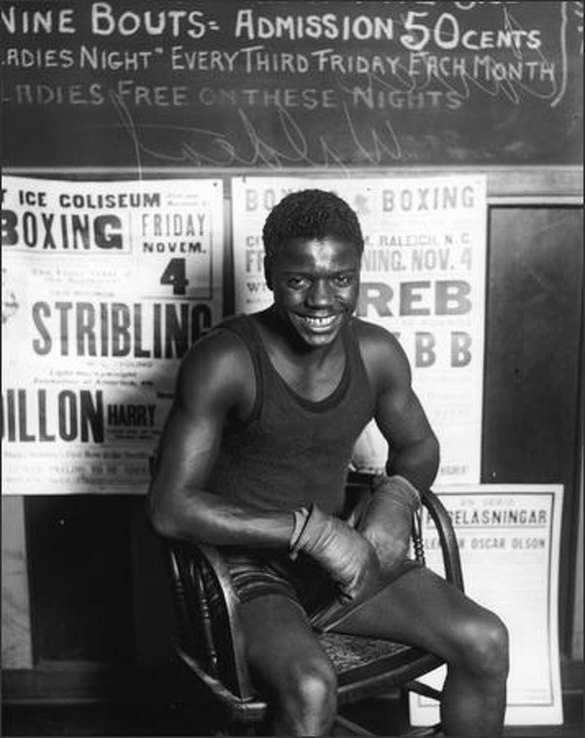 Leslie Earnest 'Wildcat' Carter began boxing at the age of 14, about the same time he moved to Seattle from Edmonton, Alberta. As a young man, he fought several veteran boxers and later became a professional boxer in the mid-1920s. He boxed internationally until the beginning of World War II when he enlisted in the Army and served as a physical education instructor until his honorable discharge. He did not box again. This photo was taken during the full-swing of his career at the Crystal Pool when he fought and beat veteran boxer Vic Foley on Nov. 22, 1927. (Seattle Post-Intelligencer Collection, Museum of History & Industry 1986.5G.262)