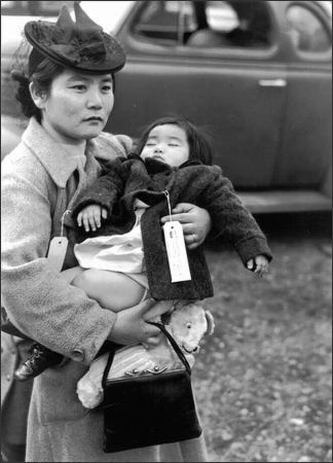 Her 11-month-old daughter asleep in her arms, Fumiko Hayashida waits to board a ferry from Bainbridge Island on March 30, 1942. The pair were being deported to an internment camp for Japanese-Americans in Manzanar, Calif. Photo: Museum Of History And Industry