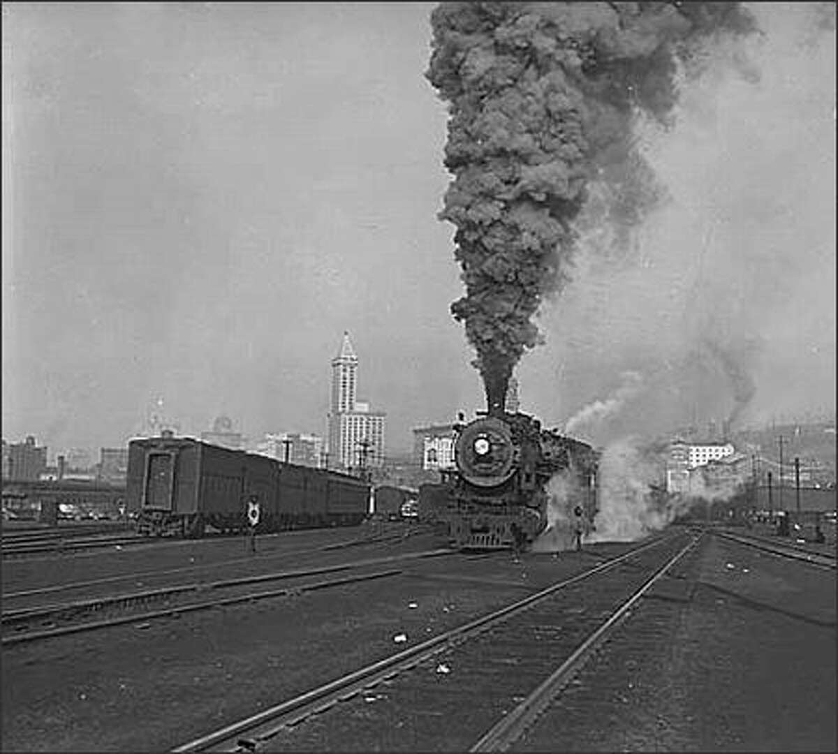 Huge railroad yards were located at large railway stations throughout the country. Here, the trains loaded and unloaded freight and passengers. They also exchanged railcars and switched tracks for the outgoing journey. This photo, taken in 1945, shows the Seattle railroad yards south of King Street Station. A steam locomotive is coming down the track, and the Smith Tower is visible in the distance. (Seattle Post-Intelligencer Collection, Museum of History & Industry PI25230)