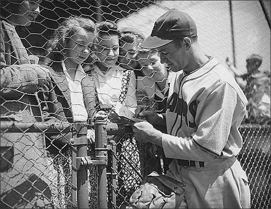 Seattle Rainiers shortstop Joe Dobbins signing autographs, Seattle, 1944. Just after the United States entered World War II, President Franklin Roosevelt decided that it would be good for the nation's morale if professional baseball games continued. Some players from the Seattle Rainiers joined the military, but the team continued to play throughout the war. In addition to their regular games, the team also played exhibition games against service ball clubs to raise money for the war effort. (Seattle Post-Intelligencer Collection, Museum of History & Industry PI26701) Photo: Museum Of History And Industry