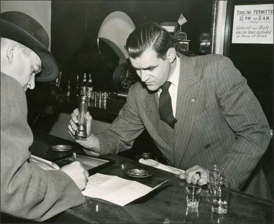 "Speakeasy raid -- In November of 1947, during what was called a ""Gold Braid"" raid, Sgt. Loren Meece, left, checks the license of Cabbies' Club, a Seattle nightclub. Holding the flashlight is Eugene Banks. Note the sign at right that says ""Dancing Permitted 12 p.m. to 4 a.m. only."" (Seattle Post-Intelligencer photo) Photo: Museum Of History And Industry"